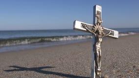 Metal crucifix on summer sea beach – religion concept stock footage