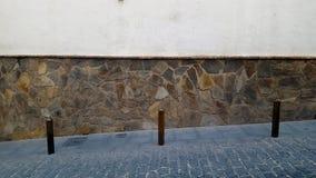 Metal cumownicy w brukującej ulicie z kamiennej ściany tłem fotografia royalty free