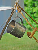 Metal Cup. Hung on wood tripod stand with rope from reenactment of War of 1812 Stock Images