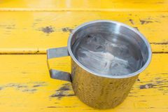 A metal cup of fresh water on yellow table Stock Photos