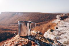 Metal cup on rock in mountain forest. Autumn colors, close up, copyspace. beautiful landscape Stock Image