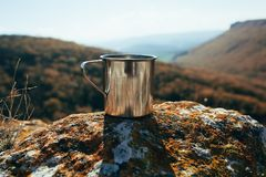Metal cup on rock in mountain forest. Autumn colors, close up, copyspace. beautiful landscape stock photo