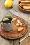 Metal cup of tea, brown sugar, crackers and lemon Stock Photo