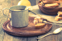 Metal cup of tea, brown sugar, crackers and lemon Royalty Free Stock Photo