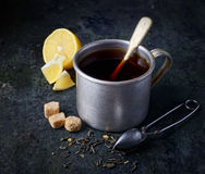 Metal cup of tea, a teaspoon,  brown sugar and a lemon on a black background Royalty Free Stock Photos