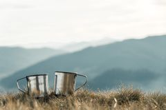 Metal cups on a background of mountains stock photography