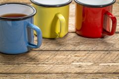 Metal cups of hot tea on a rustic picnic table Royalty Free Stock Photos