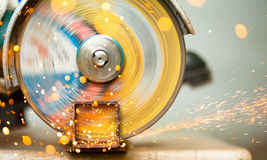 Metal cutting. Working cutoff wheel with multitude of sparks stock photo