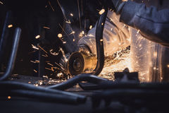 Metal cutting with a grinder. Steel pipe with flash of sparks close up. Horizontal photo royalty free stock image
