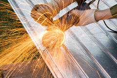 Metal cutting sparks. (Man in khaki Working under Metal Royalty Free Stock Photos