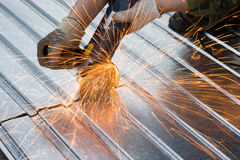 Metal cutting sparks. (Man in khaki Working under Metal Stock Photo