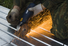 Metal cutting sparks. (Man in khaki Working under Metal Royalty Free Stock Photo