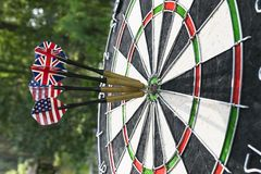 Metal darts have hit the red bullseye on a dart board. Darts Game. Darts arrow in the target center darts in bull`s eye close up. Success hitting Royalty Free Stock Photo