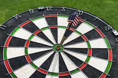 Metal darts have hit the red bullseye on a dart board. Darts Game. Darts arrow in the target center darts in bull`s eye close up. Stock Photo
