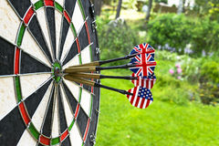 Metal darts have hit the red bullseye on a dart board. Darts Game. Darts arrow in the target center darts in bull`s eye close up. Royalty Free Stock Photography