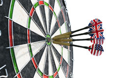 Metal darts have hit the red bullseye on a dart board. Darts Game. Darts arrow in the target center darts in bull`s eye close up. Stock Photos