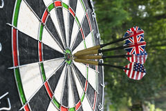 Metal darts have hit the red bullseye on a dart board. Darts Game. Darts arrow in the target center darts in bull`s eye close up. Stock Image