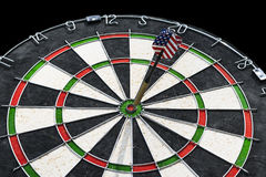 Metal darts have hit the red bullseye on a dart board. Darts Game. Darts arrow in the target center darts in bull`s eye close up. Success hitting Royalty Free Stock Images