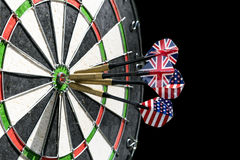 Metal darts have hit the red bullseye on a dart board. Darts Game. Darts arrow in the target center darts in bull`s eye close up. Success hitting Stock Photography