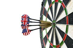 Metal darts have hit the red bullseye on a dart board. Darts Game. Darts arrow in the target center darts in bull`s eye close up. Success hitting Stock Photos