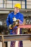 Metal de aço do corte do trabalhador da construção com moedor de ângulo Imagem de Stock Royalty Free