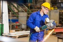 Metal de acero del corte del trabajador de construcción con la amoladora de ángulo Fotos de archivo libres de regalías
