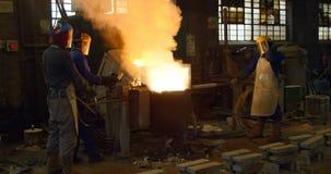 Metal de fusión del trabajador en el taller 4k de la fundición metrajes