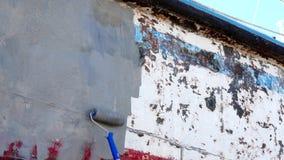 Metal de la cartilla de pinturas del trabajador de la nave oxidada vieja en el astillero en el puerto de Moscú metrajes