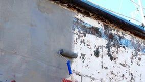 Metal de la cartilla de pinturas del trabajador de la nave oxidada vieja en el astillero en el puerto de Moscú almacen de video