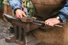 Metal de trabajo del herrero con un martillo en el yunque en la fragua Fotografía de archivo libre de regalías