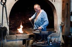 Metal de trabajo del herrero en el yunque en la fragua fotografía de archivo libre de regalías