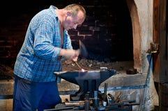 Metal de trabajo del herrero en el yunque en la fragua imagen de archivo