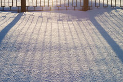 Metal decorative fence and the shadow of it falls flat lines on the snow. Royalty Free Stock Photo