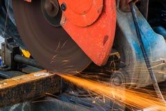 Metal del corte del trabajador con la amoladora Chispea mientras que muele el hierro Fotos de archivo libres de regalías