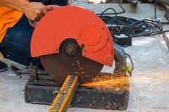 Metal del corte del trabajador con la amoladora Chispea mientras que muele el hierro Fotos de archivo