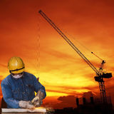 Metal del corte del trabajador de construcción con un fondo de la construcción Foto de archivo libre de regalías