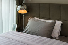 Metal desk lamp and grey pillow on bed Royalty Free Stock Photo