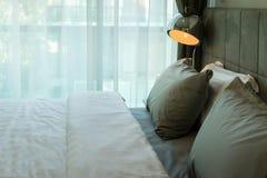 Metal desk lamp and grey pillow Stock Photo