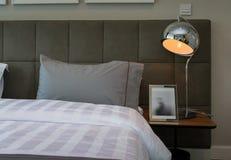 Metal desk lamp and pillow Stock Photos