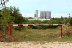 Metal destravado vermelho e rampa branca que impede o acesso à estrada que conduz para o grande complexo industrial com armazenam fotos de stock