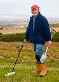 Metal detecing on moorland. A metal detectorist looking for objects lost or hidden underground on a moorland site. He has a detector, radio transmitter and stock photo
