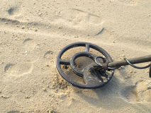 Metal detecting. Looking for coins on the beach with a metal detector Stock Image