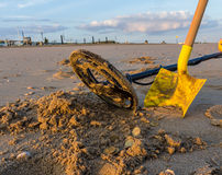 Metal detecting on a beach. Metal detector and spade with found coins in the sand royalty free stock photos