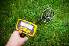 Metal detector in action. Grass background royalty free stock photo