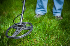 Metal detector in action. Green grass background royalty free stock photo