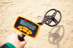 Metal detector in action. Sand background stock images