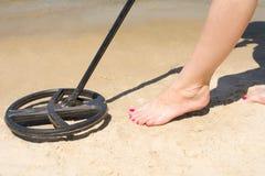 Metal detector in the sand. Metal detector treasure hunt in the sand female legs stock images