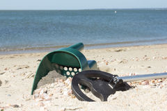 Metal detector and sand scoop on a sunny beach Stock Image