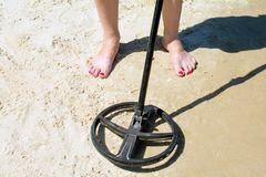 Metal detector in the sand. Metal detector treasure hunt in the sand stock images