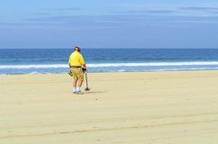 Metal detectorist on Pacific Beach. An old man walking along the coast holding a portable metal detector on the Pacific beach in America, pointing the long stick royalty free stock photos